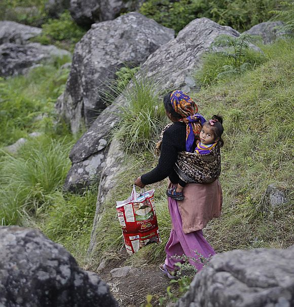 A woman carrying a baby on her back walks down a hill during a rescue operation at Govindghat