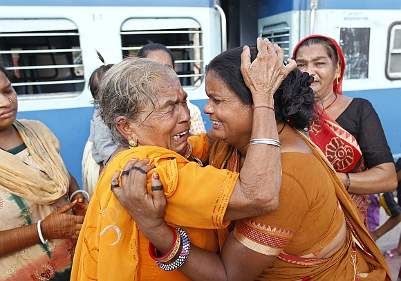 A pilgrim (in yellow) who was stranded in Uttarakhand reacts after meeting her relatives at a railway station in the western Indian city of Ahmedabad.