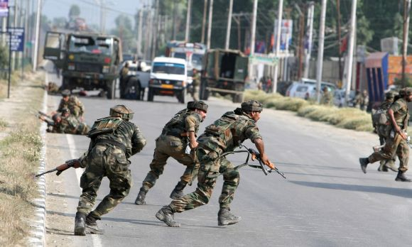 Army personnel running for cover after a militant strike on a convoy outside Srinagar on Monday