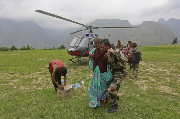 A woman is assisted by a soldier as she leaves an army helicopter during a rescue operation at Joshimat
