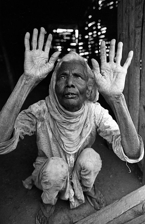 An aged blind horror-struck woman lifts her hands on October 12, 1987, near Bhopal, as she recalls the death-night of the Bhopal gas disaster which took place on December 3, 1984