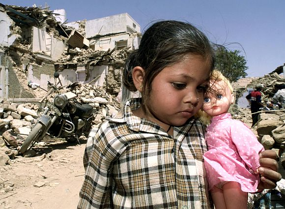 Putya, five-years-old, holds her doll while standing in front of the ruins of her house in Bhuj, April 3, 2001