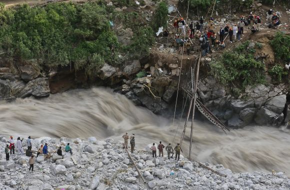 Soldiers try to repair a temporary footbridge over River Alaknanda after it was destroyed, during rescue operations in Govindghat in the Himalayan state of Uttarakhand