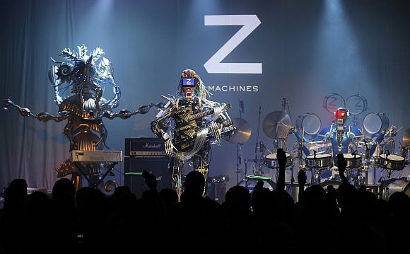 Members of the robot rock band Z-Machines, guitarist Mach (C), keyboardist Cosmo (L) and drummer Ashura perform during the band's debut live concert