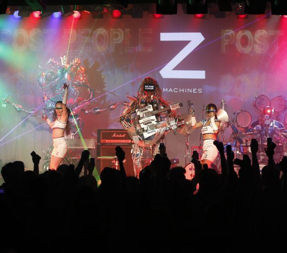 Members of the robot rock band Z-Machines, guitarist Mach (C), keyboardist Cosmo (L) and drummer Ashura perform with dancers