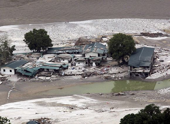 A view shows the damaged houses next to a river after heavy rains in the Himalayan state of Uttarakhand