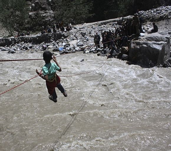 Indian Army personnel rescue a stranded child with the help of ropes through the flooded waters of a river