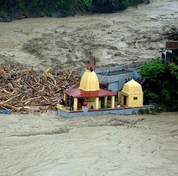 Debris carried by floodwaters of the River Alaknanda crashes against a temple in Chamoli district