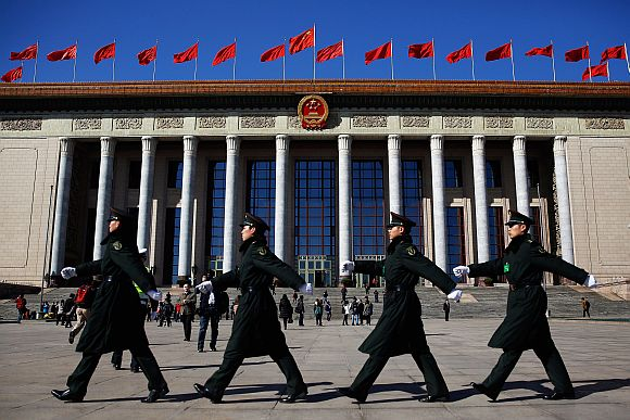 Chinese military soldiers march past the front of the Great Hall of the People after a pre-opening session of the National People's Congress