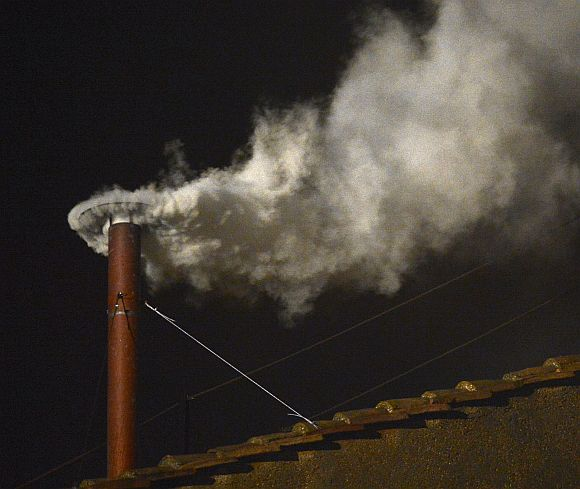 White smoke billows out of the chimney over the Sistine Chapel, announcing the election of the new Pope