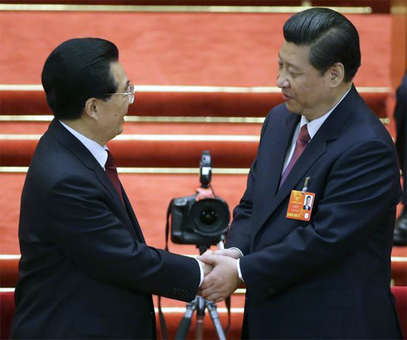 Xi Jinping shake hands with China's former President Hu Jintao during the fourth plenary meeting of the National People's Congress at the Great Hall of the People in Beijing