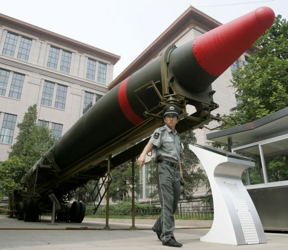 A security guard stands under the Chinese DF-2 ground-to-ground nuclear bomb at an exhibition in Beijing.