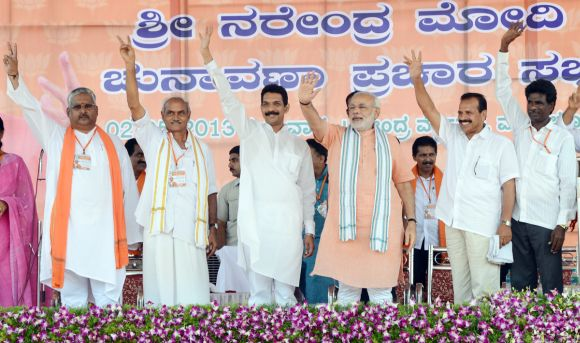 Narendra Modi gestures with BJP leaders in Karnataka during the Mangalore rally