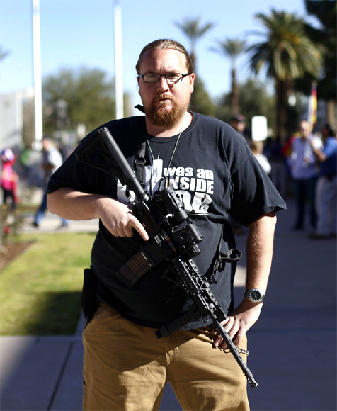 Brandon Smith poses with his AR-15 rifle during a pro-gun and Second Amendment protest outside the Arizona State Capitol in Phoenix, Arizona
