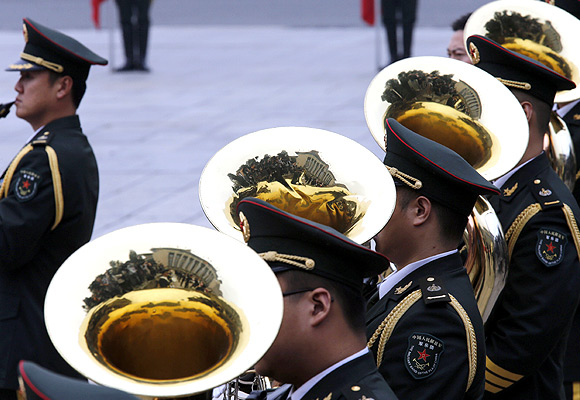 Members of a band play their instruments during an official welcoming ceremony in Beijing