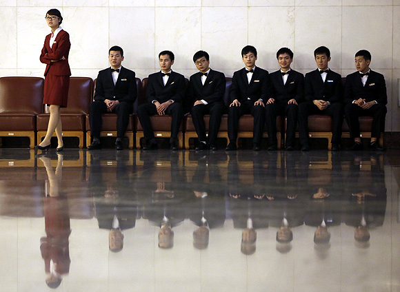 Staff members of the Communist Party of China wait at the Great Hall of the People in Beijing