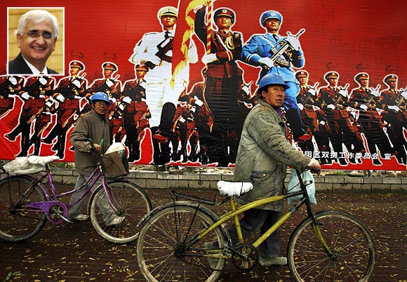 Workers push their bicycles past a billboard promoting China's People's Liberation Army in Beijing and (inset) Salman Khurshid