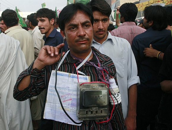 A man wears an electricity meter, a bulb and electricity bill around his neck as he takes part in a protest against power cuts in Lahore