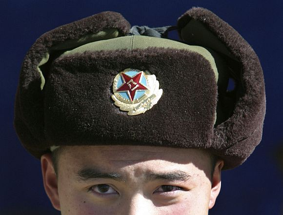 A Chinese soldier looks into the camera at the India-China trade route at Nathu-La
