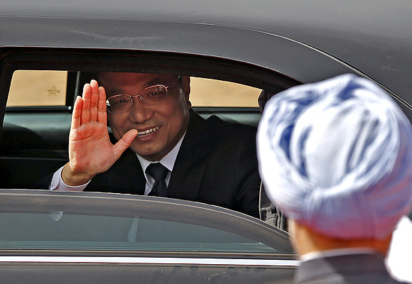 Chinese Premier Li Keqiang waves as Prime Minister Manmohan Singh watches after Li's ceremonial reception