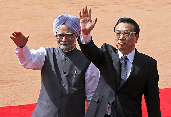 Chinese Premier Li Keqiang and Prime Minister Manmohan Singh wave towards the media during Li's ceremonial reception