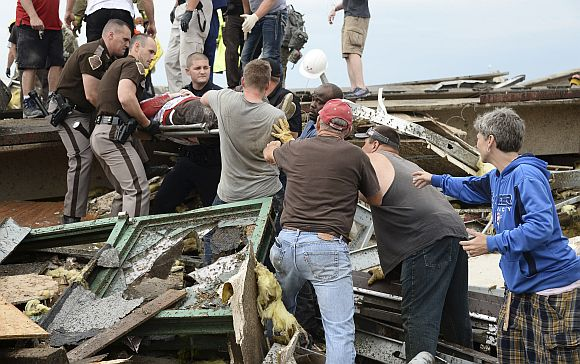 Rescue workers help free one of 15 people trapped in a medical building at the Moore hospital complex