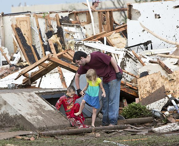 A man and two children walk through debris after the huge tornado struck Moore