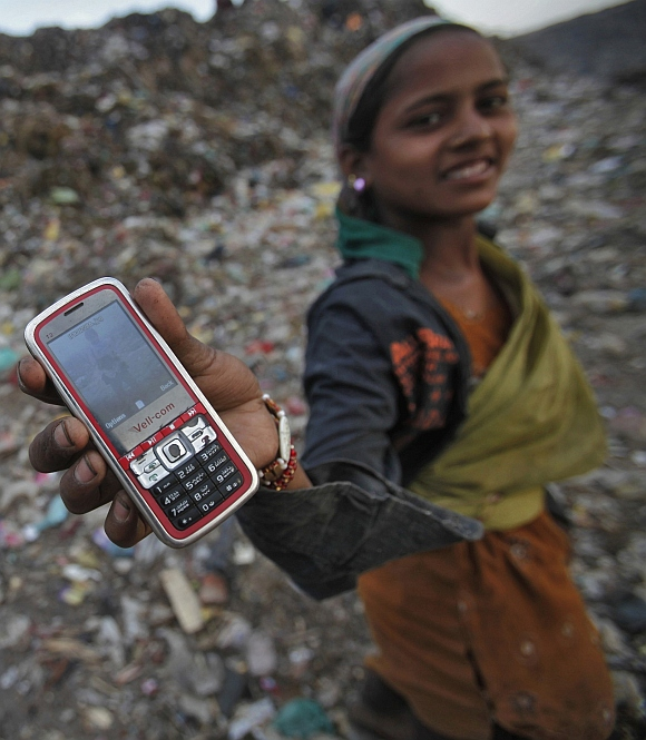 A ragpicker holds her mobile phone at a dump yard in New Delhi