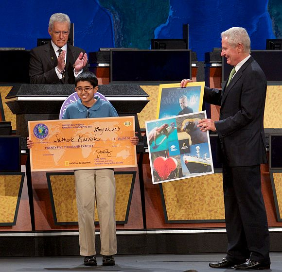 National Geographic Bee winner Sathwik Karnik, 12, of Massachusetts receives his first-place prize of a $25,000 college scholarship from National Geographic Chairman and CEO John Fahey