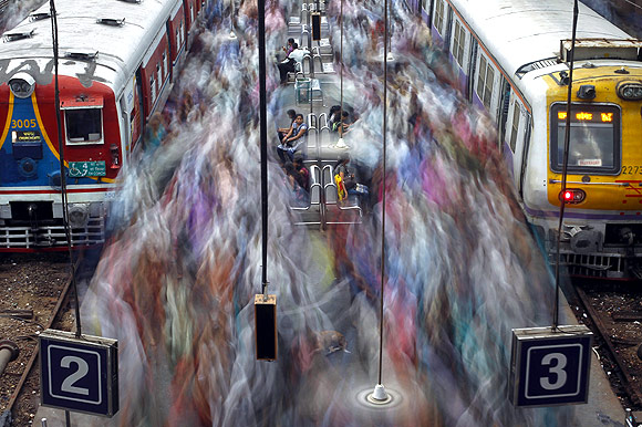 Commuters disembark from crowded suburban trains during the morning rush hour