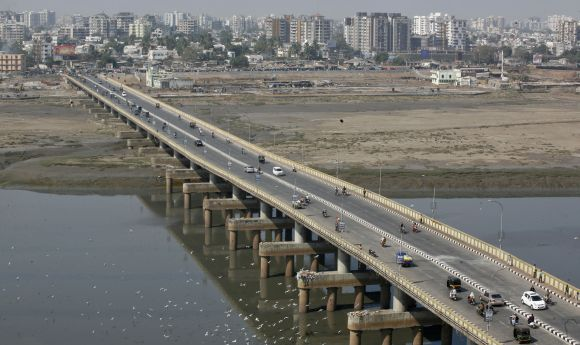 Vehicles move over a bridge built over the river Tapi in Surat