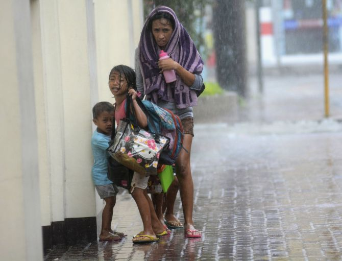 A mother takes refuge with her children as Typhoon Haiyan hits Cebu city on Friday