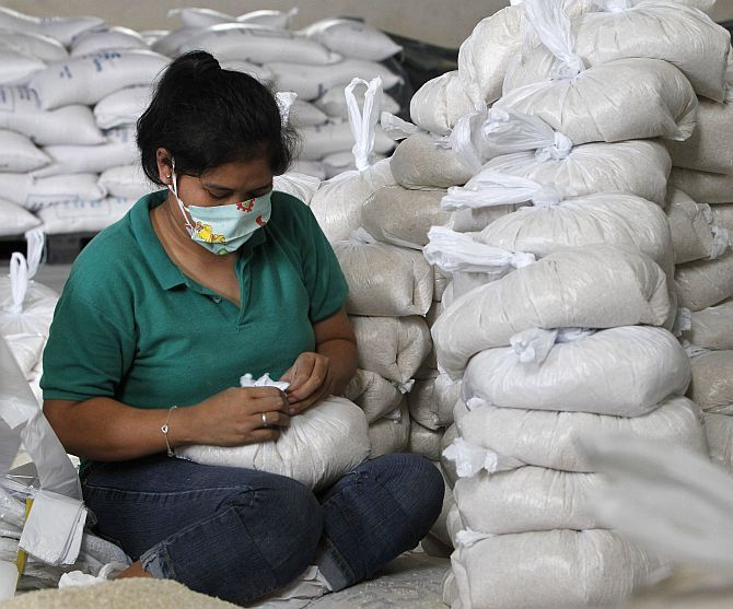 A volunteer packs rice inside a Department of Social Welfare and Development warehouse before shipping them out to the devastated provinces hit by Typhoon Haiyan, in Manila on Friday