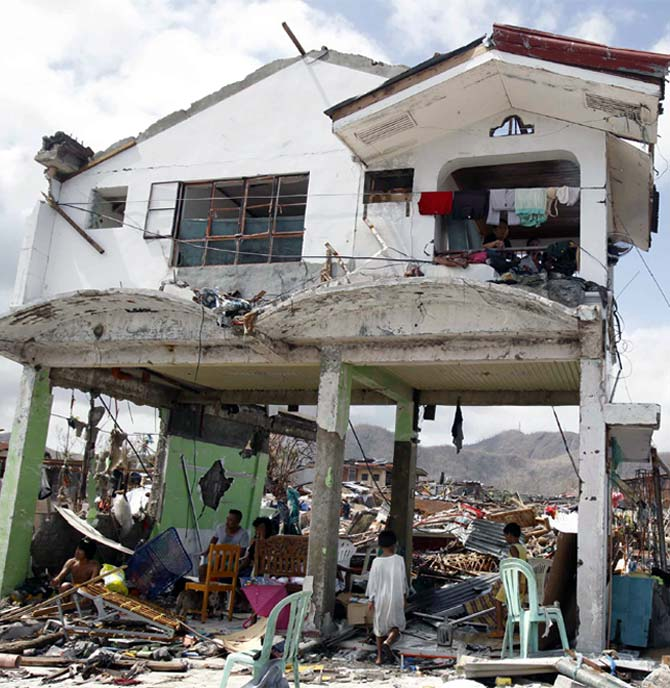 Survivors stay in their damaged house after super Typhoon Haiyan battered Tacloban city, central Philippines
