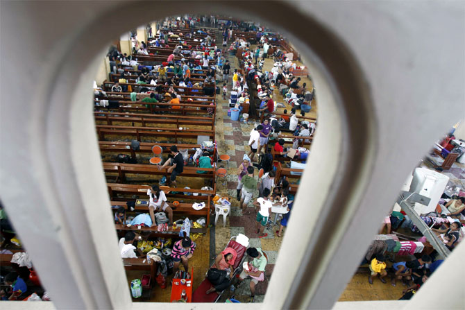 Survivors seek refuge inside a church which has been converted into an evacuation center after super Typhoon Haiyan battered Tacloban city