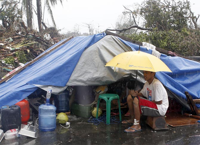 A typhoon victim sits under an umbrella outside a makeshift tent