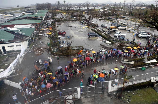 Typhoon victims queue for food and water outside the airport
