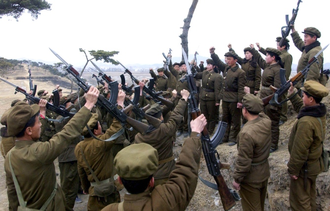 Members of the Worker-Peasant Red Guards, the civilian forces of North Korea, shout slogans in an undisclosed location in this picture released by KCNA in Pyongyang.