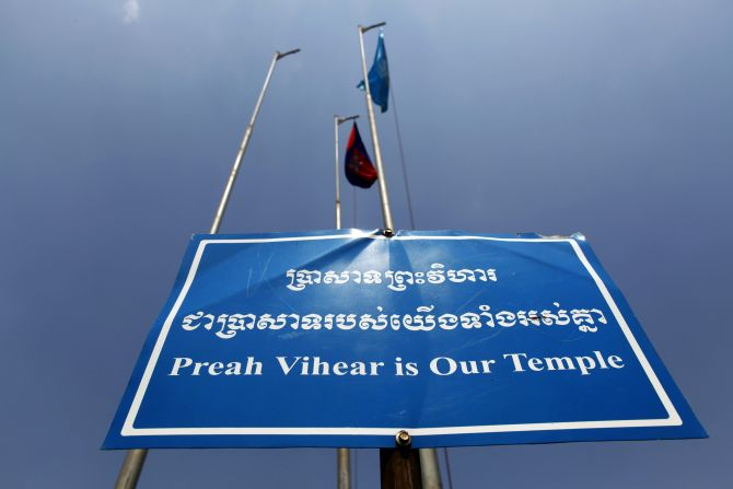 A sign is seen under Cambodian and UNESCO flags at the Preah Vihear temple