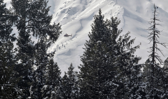 A helicopter carrying heli-skiers flies behind snow-covered trees in Gulmarg