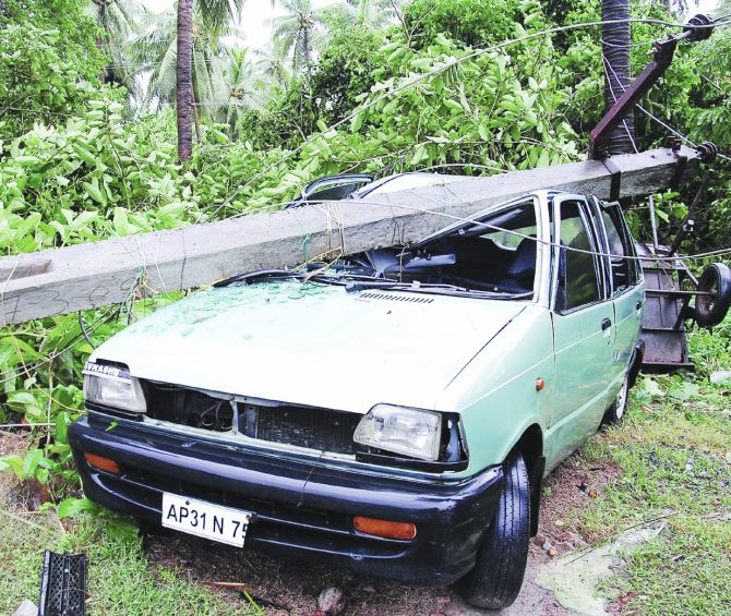 A car is seen damaged by a cyclone-hit fallen electricity pole in East Godavari district of Andhra Pradesh on Friday
