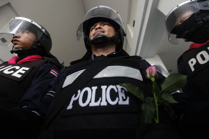 A policeman receives a flower from an anti-government protester as thousands of others gather outside the Department of Special Investigation in Bangkok