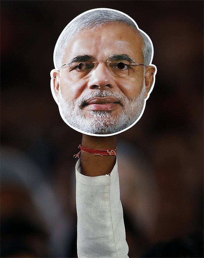 A supporter of BJP holds a mask of Gujarat CM and BJP's prime ministerial candidate Narendra Modi