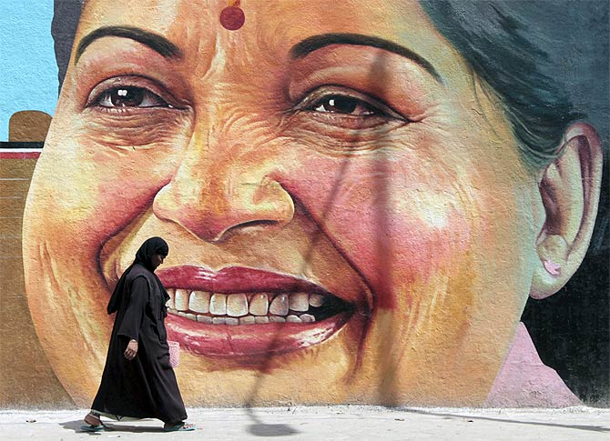 A woman walks past a portrait of Tamil Nadu Chief Minister J Jayalalithaa