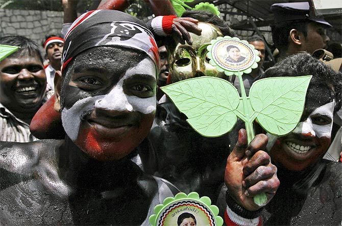 Supporters of AIADMK display the party's election symbol