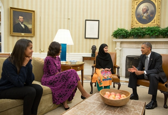 President Barack Obama, First Lady Michelle Obama, and their daughter Malia meet with Malala Yousafzai, the young Pakistani schoolgirl who was shot in the head by the Taliban a year ago, in the Oval Office