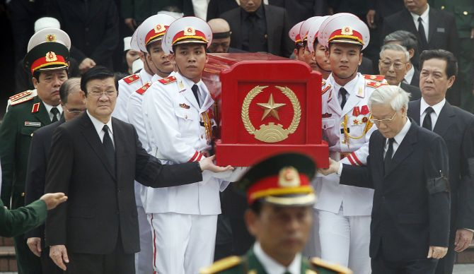 Vietnamese President Truong Tan Sang, front, left, and Prime Minister Nguyen Tan Dung, right, along with other leaders and soldiers carry the coffin of the late General Vo Nguyen Giap during his funeral in Hanoi.