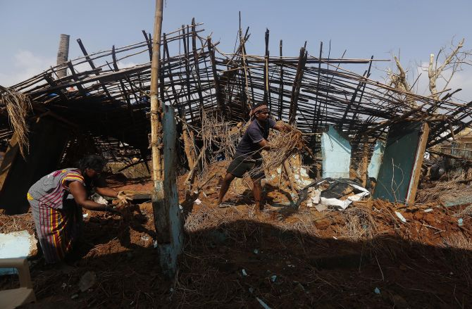 A fisherman and his wife clear the debris from their damaged house after Cyclone Phailin hit Gopalpur village in Ganjam district
