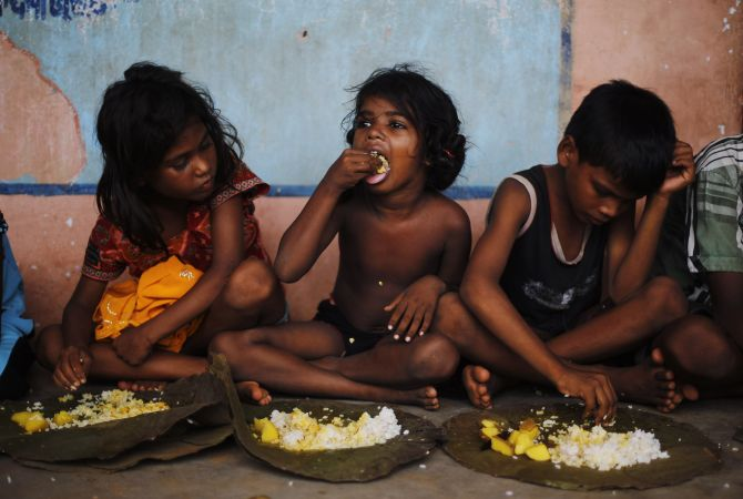 Children eat their lunch in a free meal centre at the cyclone-hit Gopalpur village