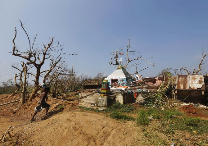 A man carries his belongings on Monday as he walks past a damaged temple after Cyclone Phailin hit Arjyapalli village
